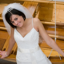 Cute bride with a wooden boat at the Hagerty Center by Traverse City Wedding Photographer Thomas Kachadurian