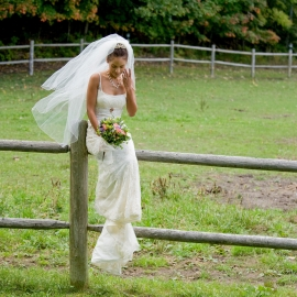 Bride on a fence by Traverse City Wedding Photographer Thomas Kachadurian
