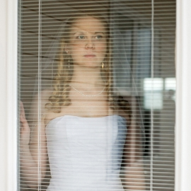 Bride looking through the blinds by Traverse City Wedding Photographer Thomas Kachadurian