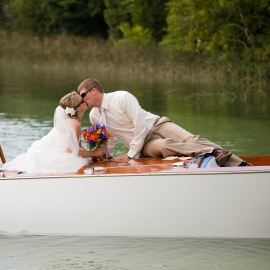 Wedding kiss on a classic Cris Craft by Traverse City Wedding Photographer Thomas Kachadurian